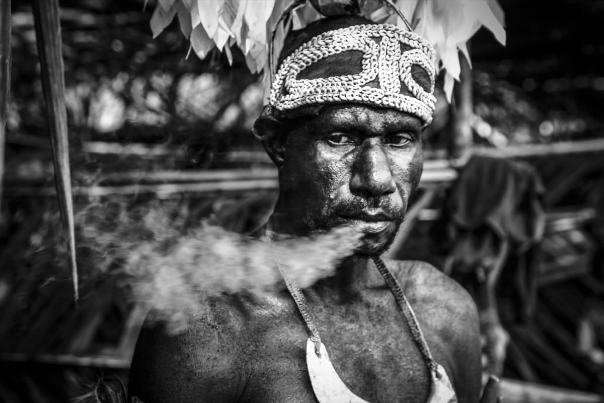 Papua New Guinea canibalism man smoking tribe