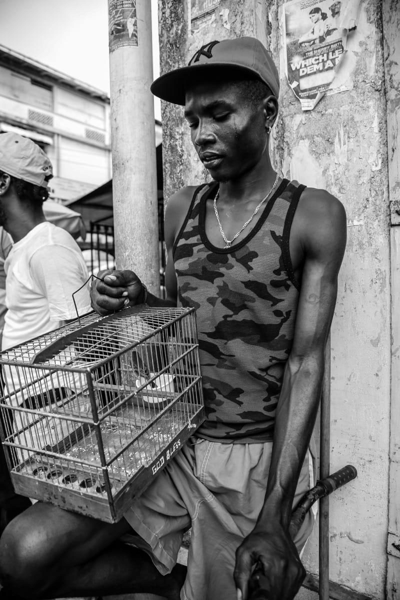Guyana man with bird cage